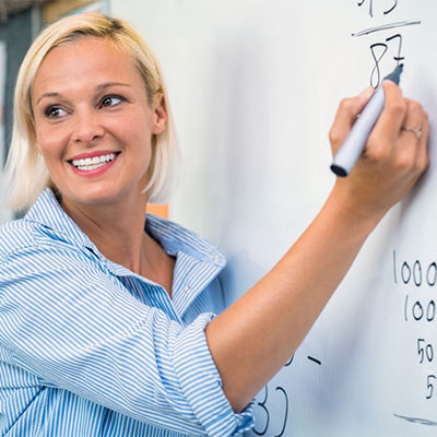 Teacher writing on-board and smiling