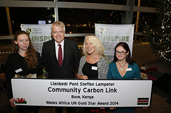 Welsh First Minister Carwyn Jones presents the UN Gold Award to project representatives Rosie Scannell, Luci Attala and Abi Jenkins.